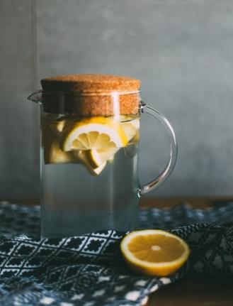 Glaskanne, Korkdeckel, kaltes Wasser mit Zitronenscheiben auf Tisch mit Tischdecke